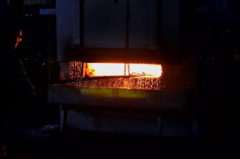 Växtarbetaren hårdnar metallen i en enorm glödhet panna i produktionseminariet av växten arkivfoton