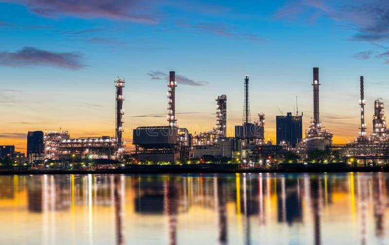 Växten för bransch för fossila bränslenraffinaderiet med blänker belysning och soluppgång i morgonen, fabrik av industriella oljo arkivbild