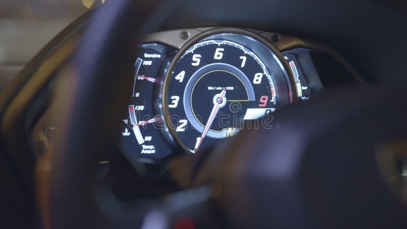 Våg av apparater på en bilinstrumentbräda med kulöra ljus materiel Apparatmakt i en sportbil Bilinstrumentbräda royaltyfri fotografi