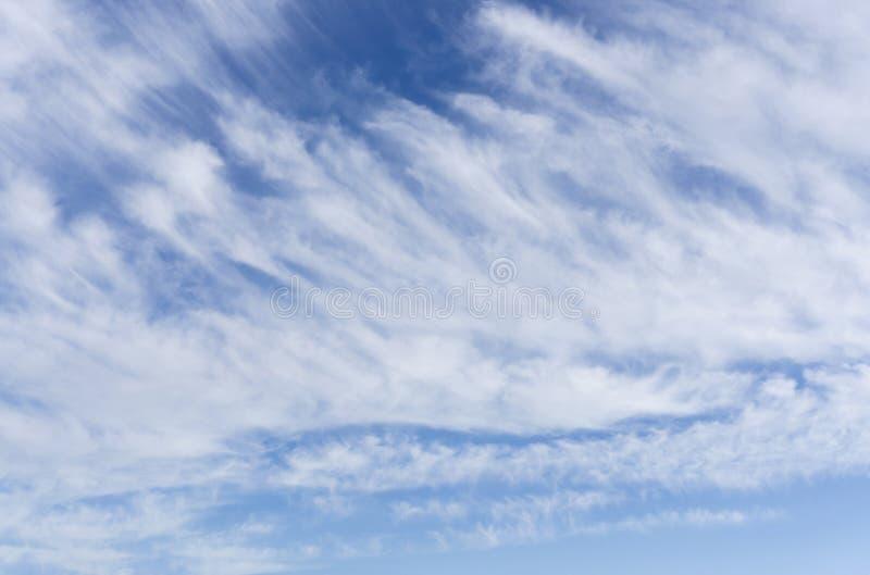 Våg av hjärtegoda mannen och vita fluffiga moln under djupblå himmel arkivbild