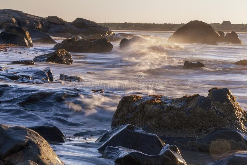 Våg för rörelsesuddighet som bryter stenig shorelinesoluppgång royaltyfri bild