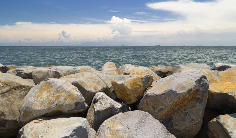 Vågbrytarestenar på sjösidan i den Manila fjärden, Filippinerna royaltyfri fotografi