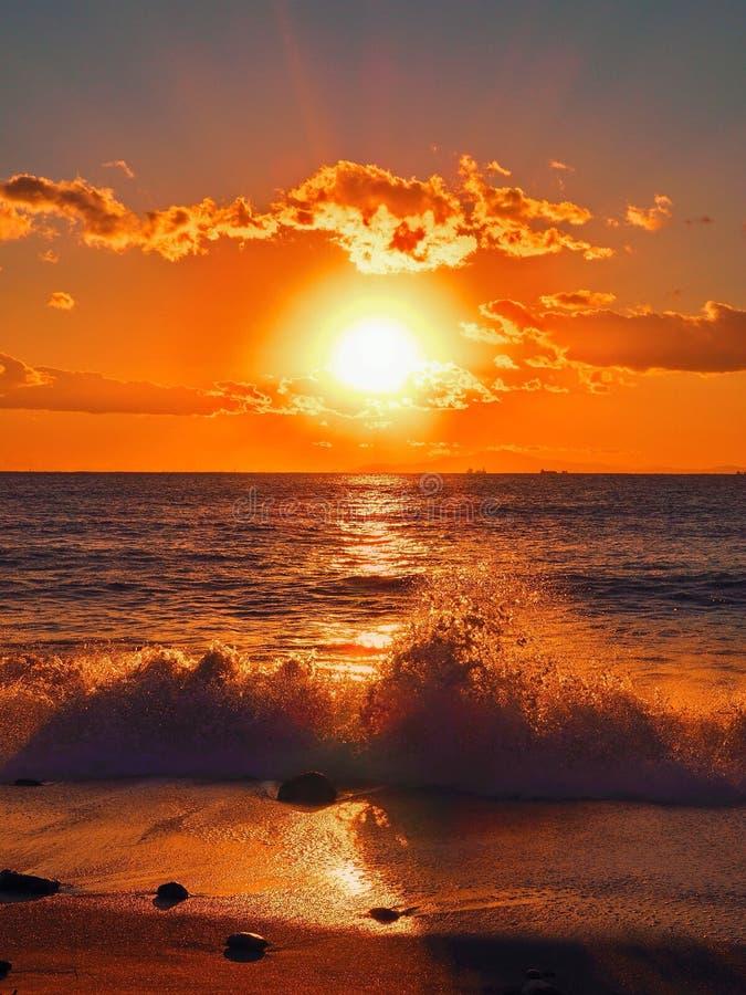 Vågen bryter framme av strandsolnedgång arkivbilder