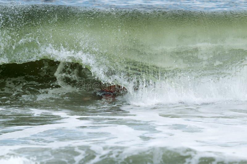Vågen krullar över mansimning i Atlanticet Ocean av av brand I arkivbild