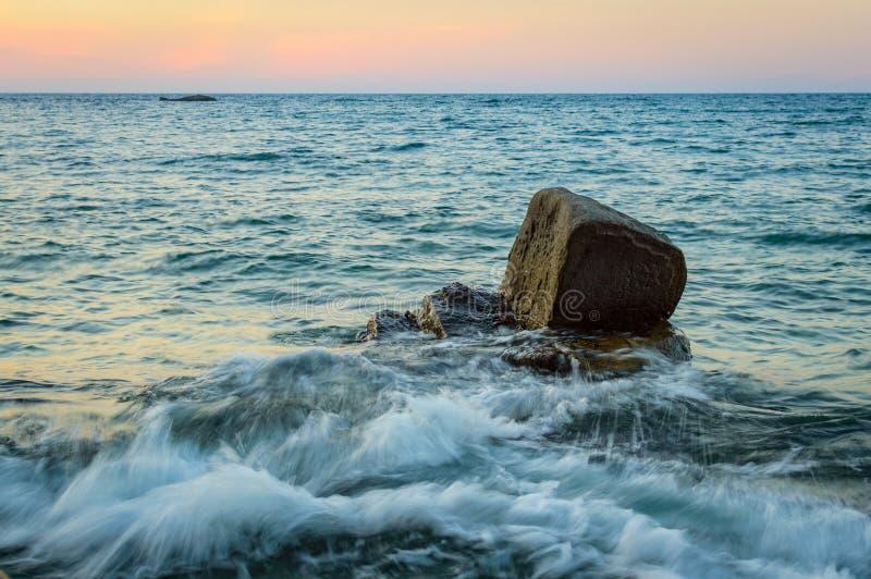 Vågfärgstänk i havet mot stenen royaltyfri fotografi