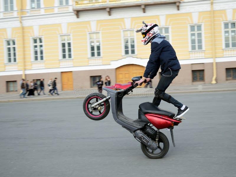 Våghalsig chaufför på en motorisk sparkcykel royaltyfria bilder