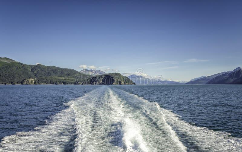Vågor bak kryssningskeppet över berg nära Seward, Alaska royaltyfria foton