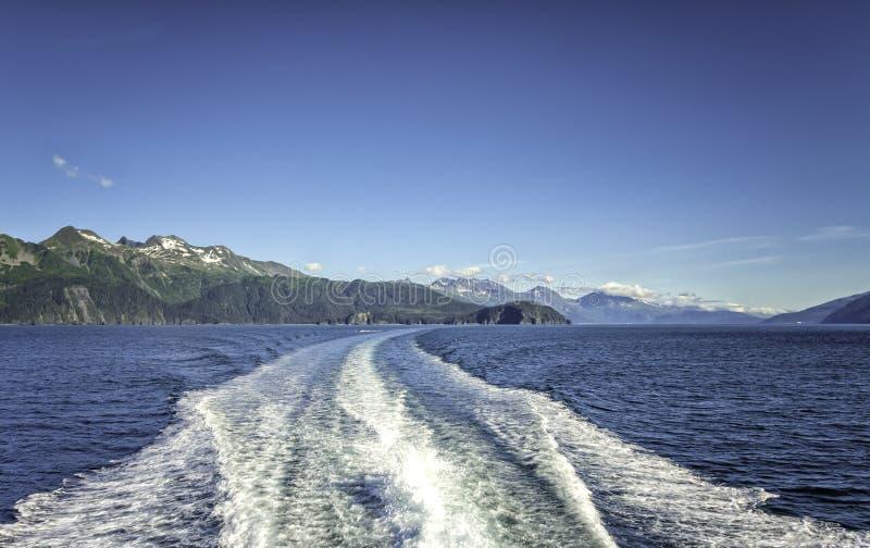 Vågor bak kryssningskeppet över berg nära Seward, Alaska arkivbilder