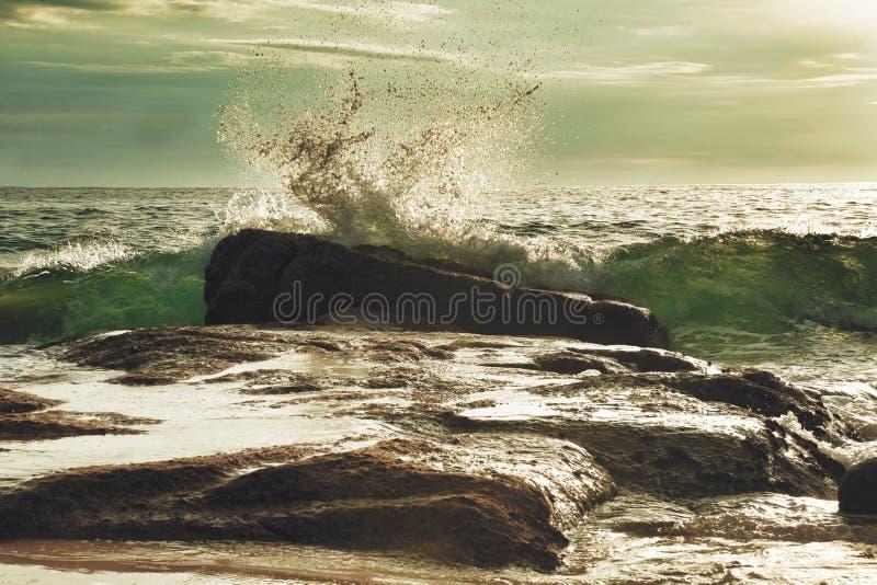 Vågor bryter vid en sten royaltyfria foton
