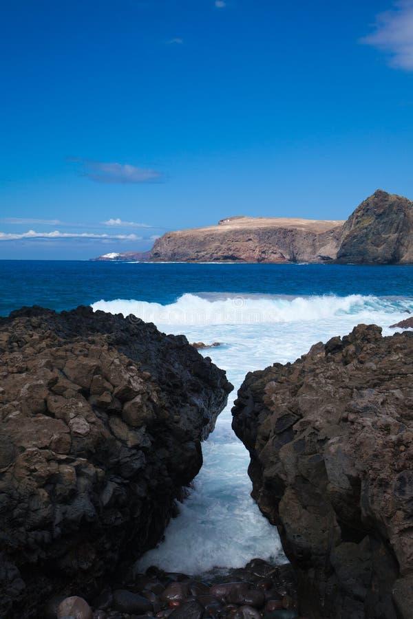 Vågor förbi den steniga kusten royaltyfri foto