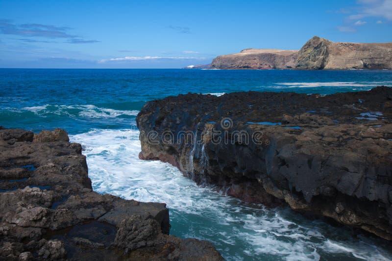 Vågor förbi den steniga kusten royaltyfria foton