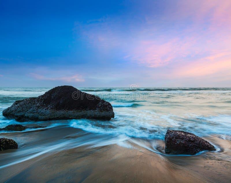 Vågor och vaggar på stranden på solnedgång arkivbilder