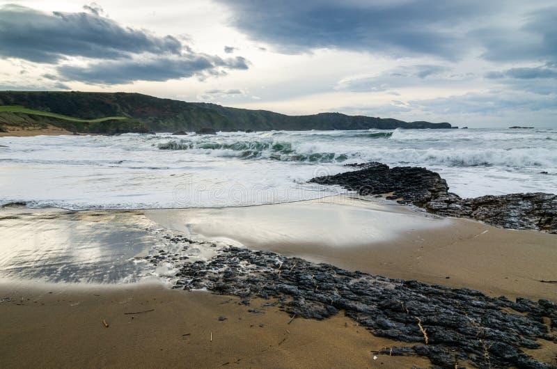 Vågor på kusten i Verdicio sätter på land i Asturias Spanien Det krabba havet i en jungfrulig strand med vaggar och skum på afton arkivfoton