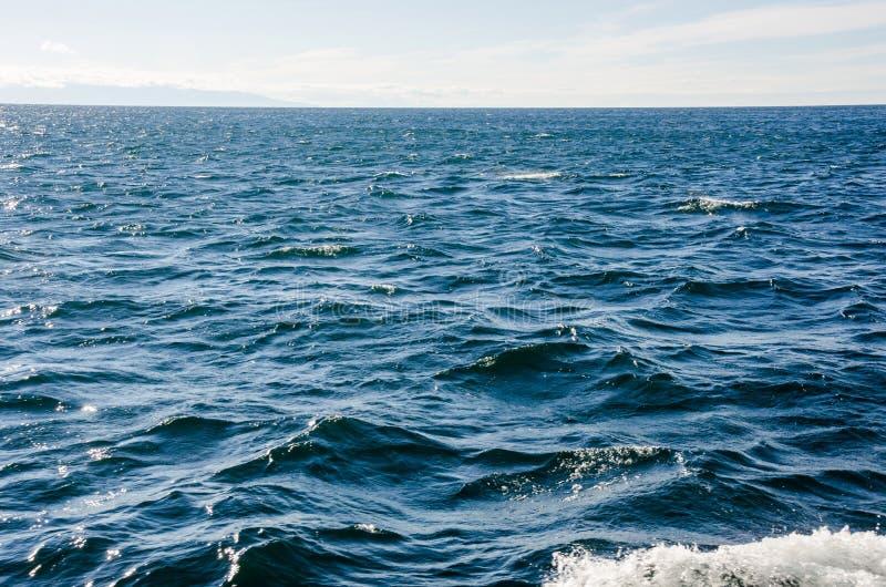Vågor på yttersida av vatten med molnig himmel royaltyfri bild
