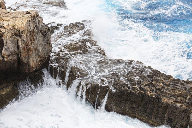 Vågor som bryter över en stenig avsats royaltyfri bild