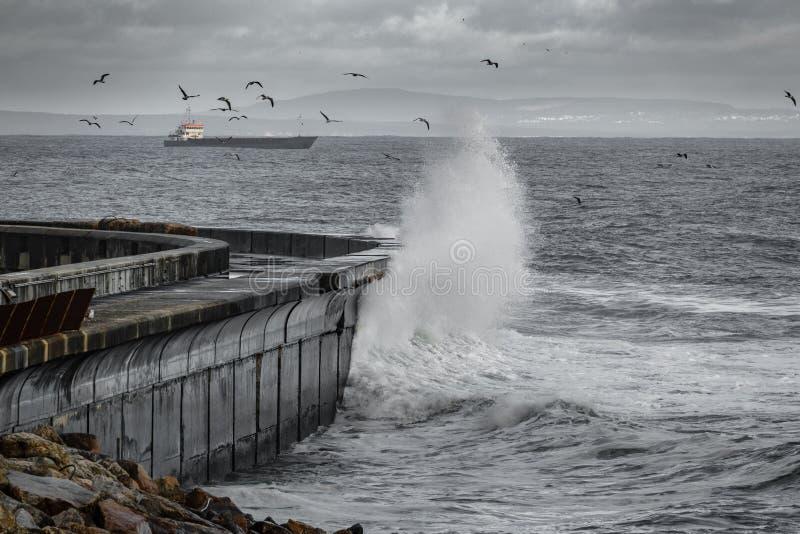Vågor som bryter över vågbrytaren arkivfoton