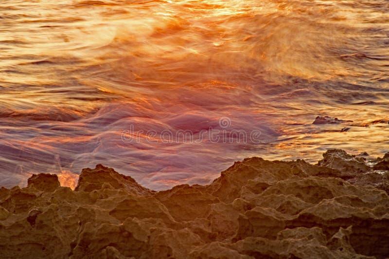 Vågor som göras suddig i ljuset av soluppgången arkivbild