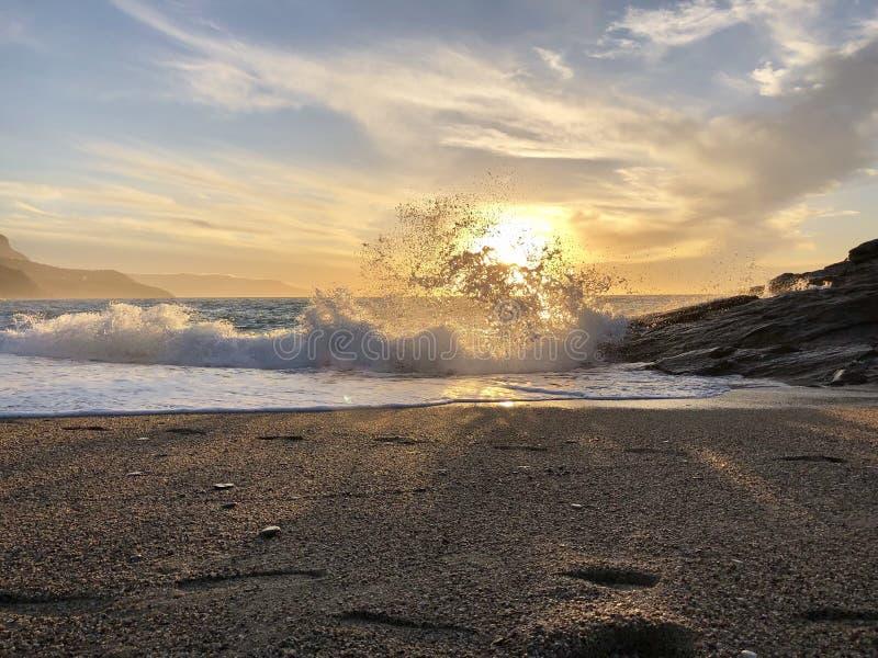 Vågor som kraschar i guld- timme arkivfoto