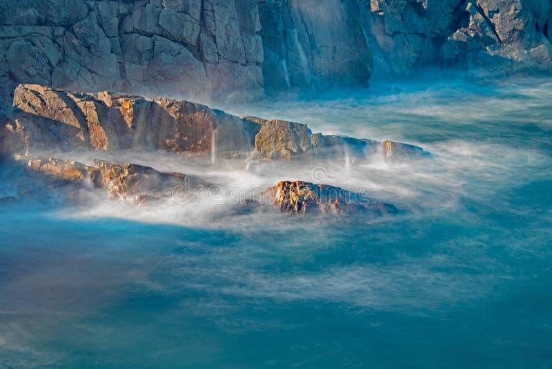 Vågor som kraschar mot fast, vaggar på uddeBreton arkivfoton