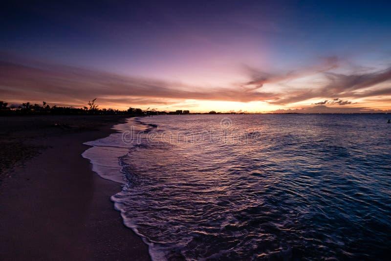 vågor som kraschar på stranden under solnedgång Härliga orange lilor s royaltyfri bild