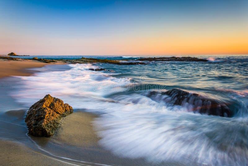 Vågor som kraschar på, vaggar på solnedgången, på Victoria Beach arkivfoton