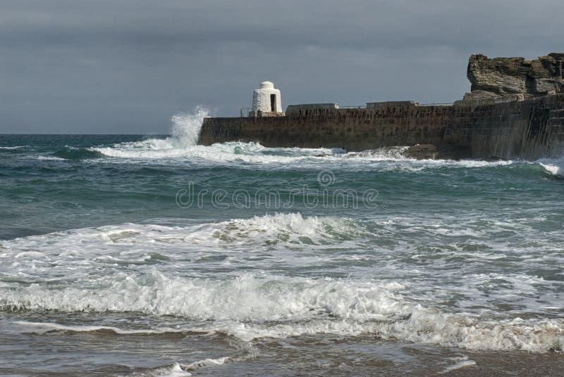 Vågor som kraschar pir på Portreath, Cornwall UK arkivbild