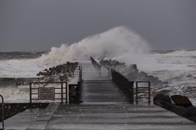 Vågor som slår mot pir under stormen i Nr Vorupoer på Nordsjönkusten arkivbilder