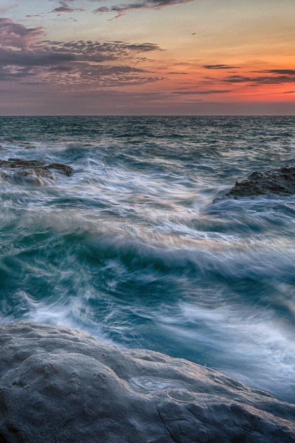 Vågor som slår stenar vid soluppgång royaltyfri fotografi