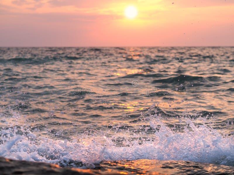 Vågor som slår steniga kuster på solnedgången royaltyfri fotografi