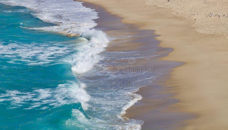 Vågor som sveper på en sandig strand - bild royaltyfri bild