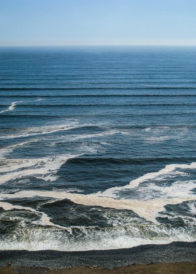Vågor som trycker på strandsanden arkivbilder