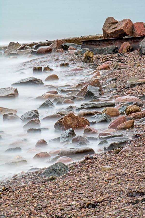 Vågor tvättar vaggar på shorelinen av fjärden av Fundy royaltyfri bild