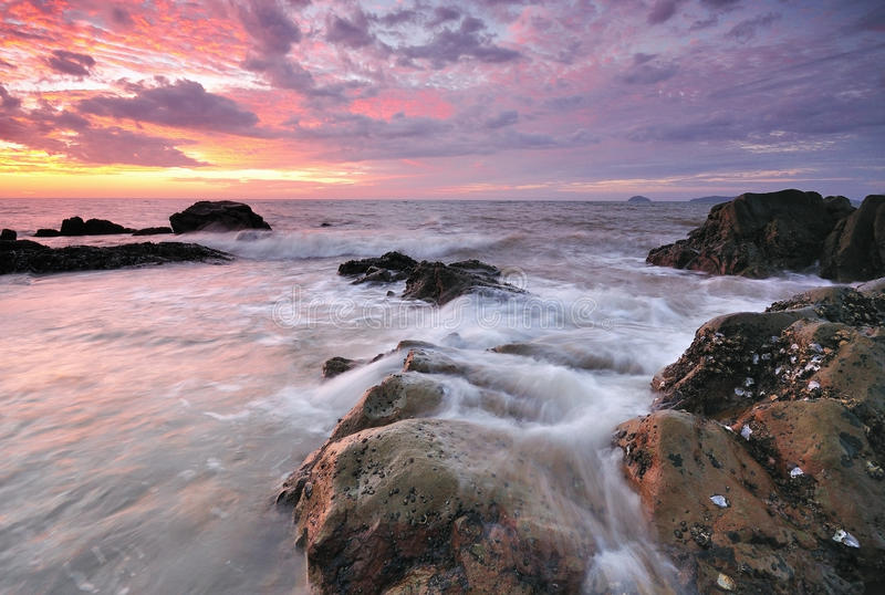Vågor vaggar och solnedgången arkivfoto