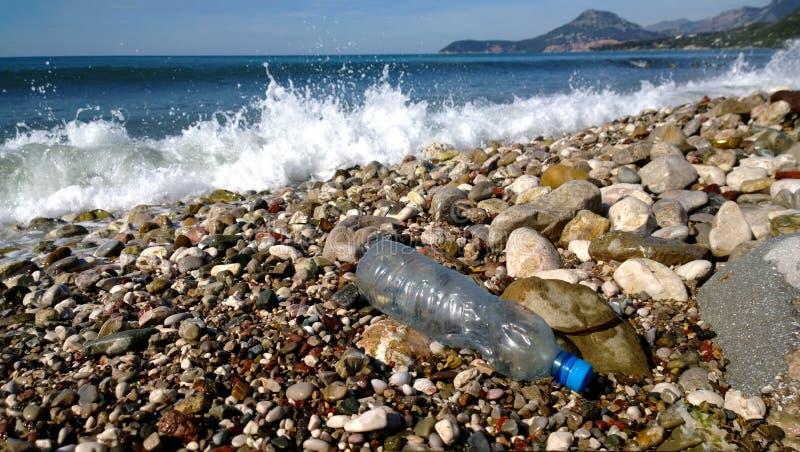 Vågorna av havet tvättade sig upp en tom plast- flaska Miljöbelastning - avskräde i sceniska fläckar royaltyfria foton