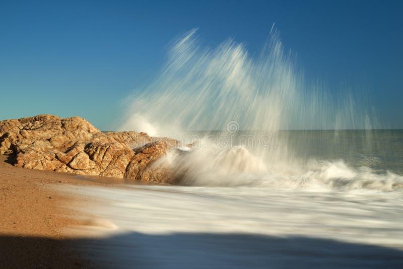 Vågorna bryter mot en stenstrand och bildar en spray arkivfoto