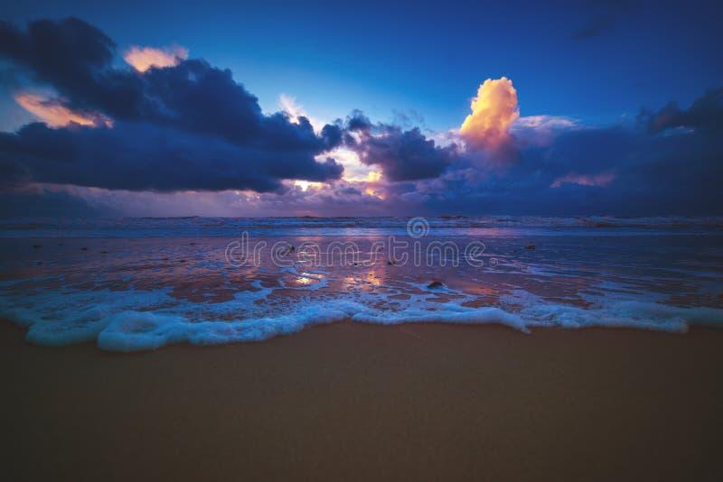 Vågrullning på stranden på en solnedgång i Danmark arkivbilder