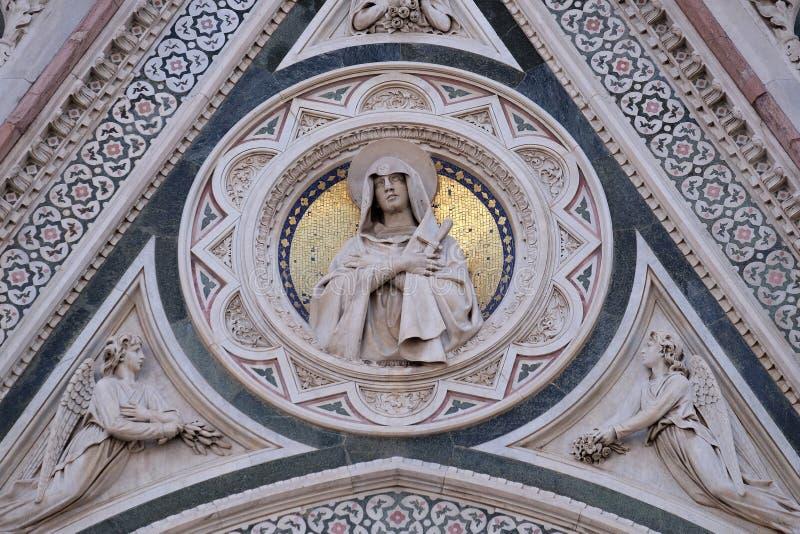 Vår dam av sorger som stöttas av änglar uthärda blommor, portal av Florence Cathedral arkivfoton