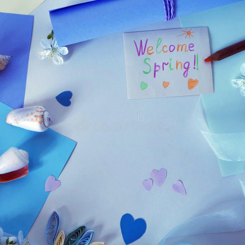 Vår för välkomnande för hälsningkort, hjärtor som göras av rosa och blått papper på en ljus bakgrund arkivfoton