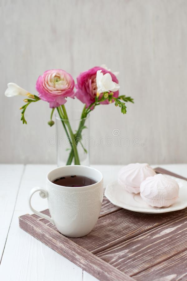Vår sommarstillebenplats En kopp te i en vit kopp Därefter är en bukett med vit freesia och rosa ronunculuses därefter royaltyfria foton
