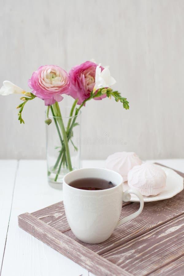 Vår sommarstillebenplats En kopp te i en vit kopp Därefter är en bukett med vit freesia och rosa ronunculuses därefter royaltyfri foto