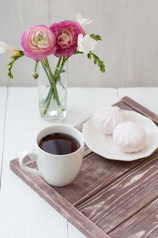 Vår sommarstillebenplats En kopp te i en vit kopp Därefter är en bukett med vit freesia och rosa ronunculuses därefter royaltyfri fotografi