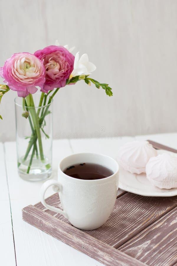 Vår sommarstillebenplats En kopp te i en vit kopp Därefter är en bukett med vit freesia och rosa ronunculuses därefter royaltyfria bilder
