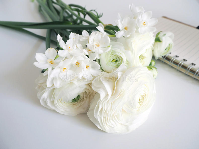 Vår utformat materielfoto Stilleben med påskliljor och persiska smörblommablommor, pingstlilja, Ranunculus och anteckningsbok arkivfoton