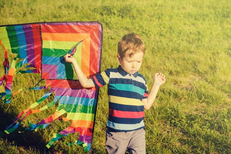 Vårbegreppsidé, vårbakgrundsmiljö som är miljö- Draken i sommarpojken som spelar på fält, parkerar dagen, barndom royaltyfria bilder