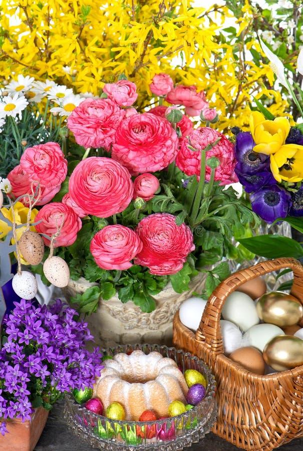 Vårblommor med den easter kakan och ägg arkivbilder
