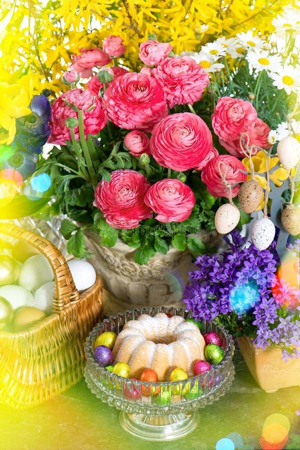 Vårblommor med den easter kakan och ägggarnering Ljusläckor arkivfoto