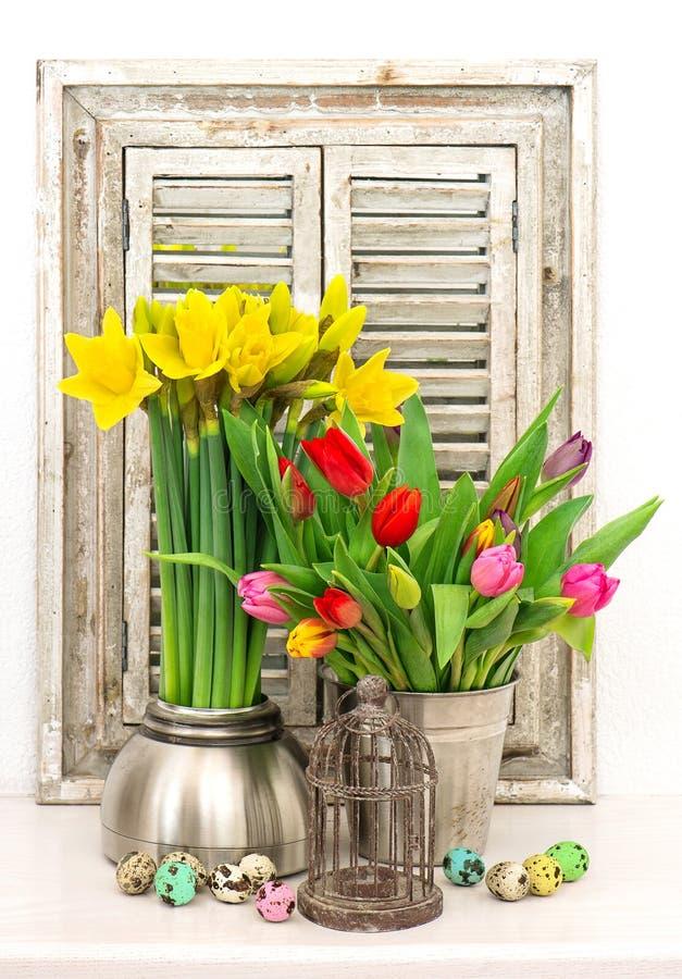 Vårblommor och kulöra easter ägg Tulpan och pingstlilja royaltyfri bild