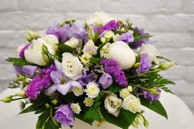 Vårbukett av blommor i stilfull hattask på den vita tabellen royaltyfri bild
