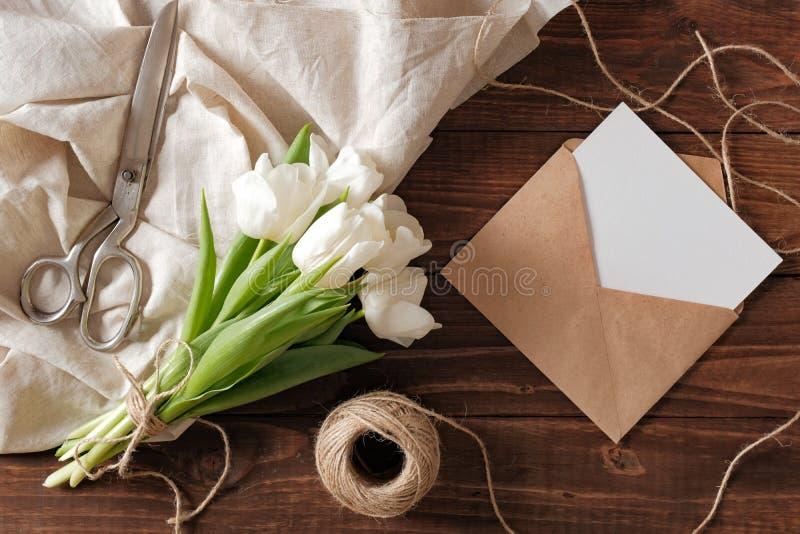 Vårbuketten av vita tulpanblommor, det kraft kuvertet med det tomma kortet, sax, tvinnar på den lantliga trätabellen Composi för  royaltyfria foton