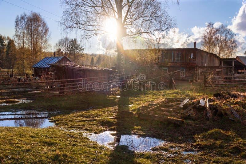 Vårbygdlandskap Solstrålar och pölar i byn royaltyfri bild